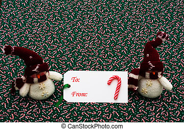 Happy Holidays - A blank gift tag with a snowman on a candy...
