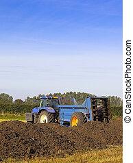 manure spreader - a manure spreader in a field in summer
