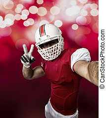 Football Player with a red uniform making a selfie on a red...