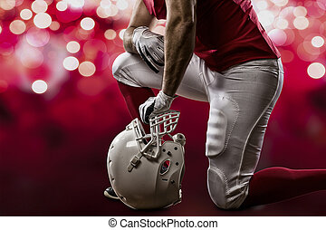 Football Player with a red uniform on his knees, on a red...