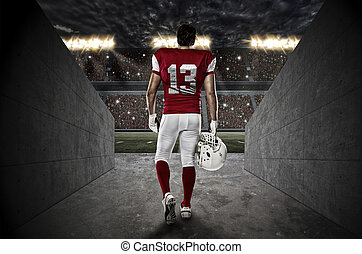 Football Player with a red uniform walking out of a Stadium...