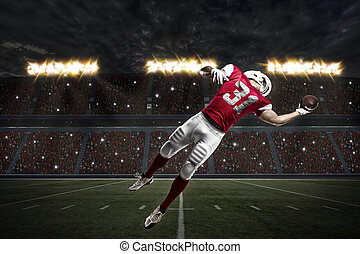Football Player with a red uniform catching a ball on a...