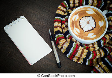 Cup of coffee surrounded the warm scarf  and note book