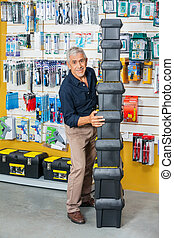 Man Stacking Toolboxes In Hardware Store - Full length of...