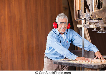 Senior Carpenter Cutting Wood With Bandsaw - Portrait of...