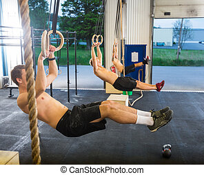 Athletes Dangling On Gymnastic Rings in Box - Full length of...