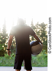 Fit Man Carrying Medicine Ball - Rear view of fit man...