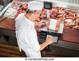 Butcher Weighing Sausages At Display Cabinet - High angle...