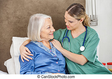 Female Caretaker Comforting Senior Woman