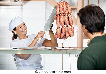 Butcher Selling Sausages To Male Customer - Happy female...