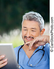 Male Doctor Smiling While Looking At Tablet Computer