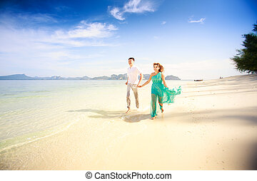 young happy asian couple on honeymoon - young handsome man...