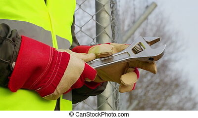 Worker with adjustable wrench at outdoors near fence