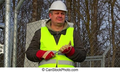 Worker with adjustable wrench at the fence