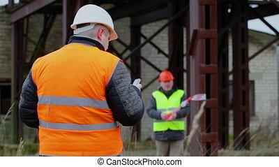 Building inspector with cell phone and with worker in...