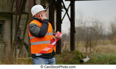 Worker with warning tape and cell phone