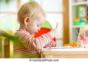 kid painting at home or nursery - smiling kid boy painting...