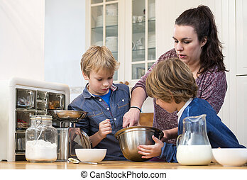 Family Mixing Cupcake Batter In Kitchen