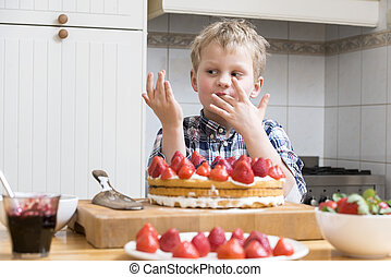 Boy Licking Finger with Strawberry Cake batter behind a...