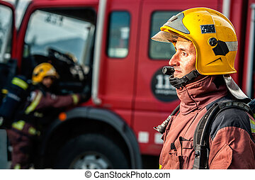 Fireman staring at fire in front of truck.