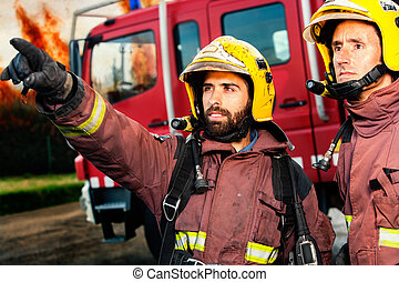 Firemen about to take action. - Firemen with fire truck and...