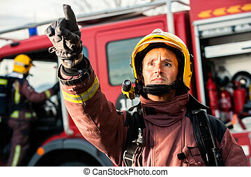 Anxious fireman pointing at fire. - Anxious fireman with...