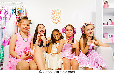 Charming girls with hair-curlers sitting on sofa - Beautiful...