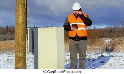 Electrical Engineer with cell phone near electric enclosure