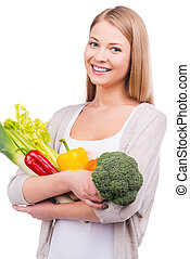 Only fresh veggies for my dinner. Beautiful young woman holding different vegetables in hands and looking at camera while standing against white background