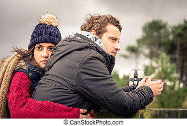 Young couple embracing and having hot beverage outdoors -...