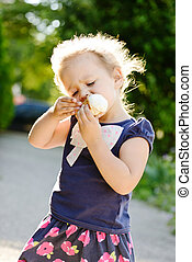 little girl eating an ice-cream in the summer