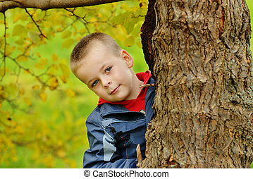 peekaboo - little boy hiding behind the tree