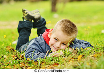 boy on meadow - toddler boy lying on the meadow
