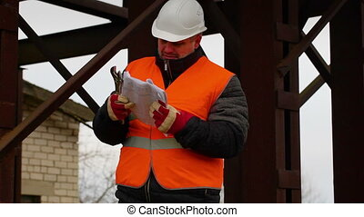 Foreman with documents and adjustable wrench in factory