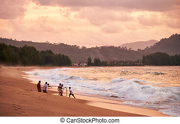 Sunset on Mai Khao beach in Phuket - People fishing at the...