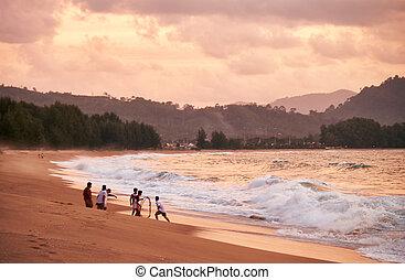Sunset on Mai Khao beach in Phuket - People fishing at the...