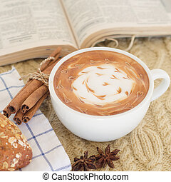 A cup of coffee with latte art and croissant on a knitted...