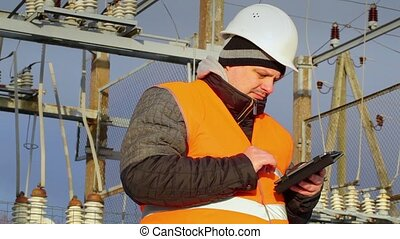 Electrical Engineer working with tablet PC in substation