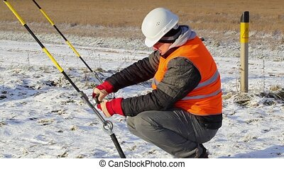 Worker with adjustable wrench near tensioner at outdoor