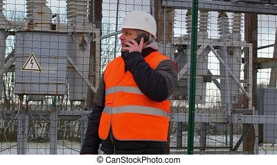 Electrical Engineer with cell phone in the electric...