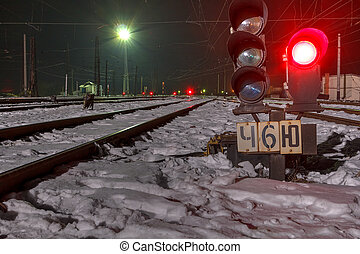 Railway traffic signal at the station at night in winter