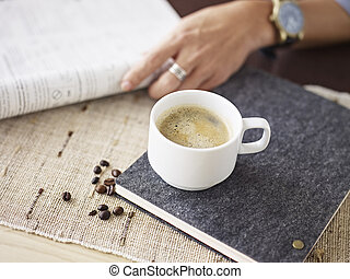 man reading - cup of coffee on table next to a man who is...