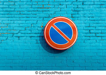 No parking sign on a blue brick wall