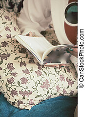 Woman reading book on the couch