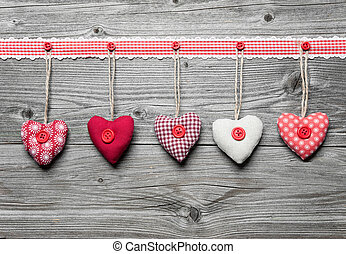 Red hearts hanging over old wood background. Valentine's Day...