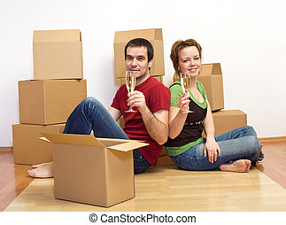 Couple toasting in their new home sitting on the floor