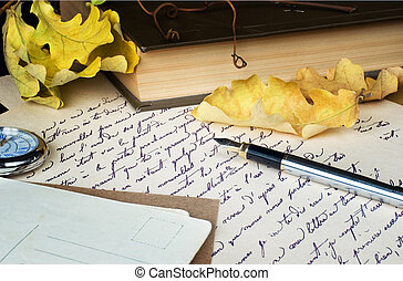 old letter, pen, book and yellow leaves - still life with an...