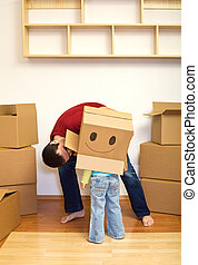 Father and little girl playing with cardboard boxes
