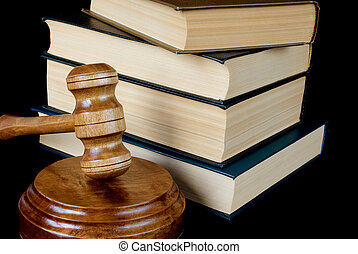 Wood gavel, soundblock and stack of thick old books