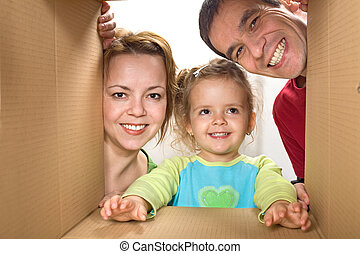 Happy family looking through a cardboard box